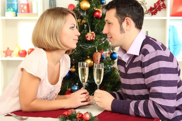 Jonge gelukkige paar glazen met champagne houden aan tafel in de buurt van de kerstboom