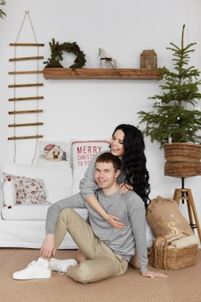 Jonge gelukkige paar glimlachend model meisje en een knappe jonge man poseren in woonkamer ingericht voor n...