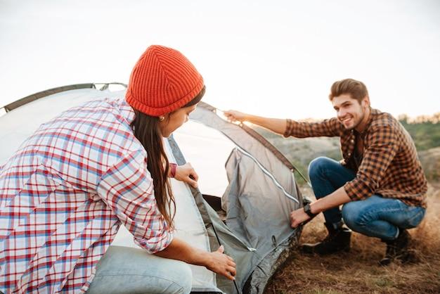 Jonge gelukkige paar het opzetten van een tent buiten bij zonsondergang