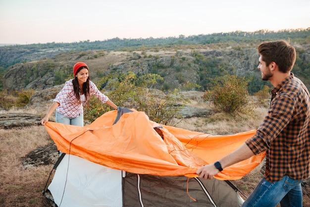 Jonge gelukkige paar het opzetten van een tent buitenshuis