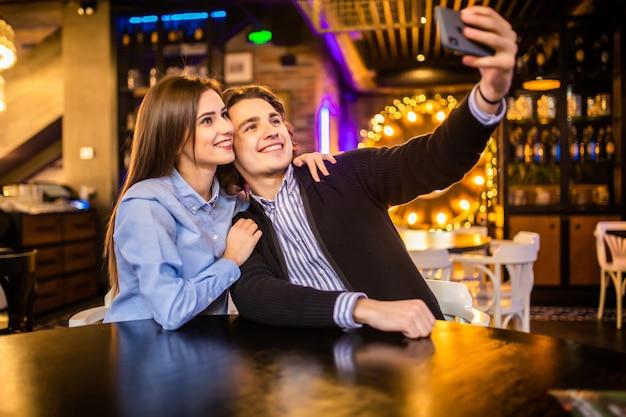 Jonge gelukkige paar in het café selfie te nemen in het café
