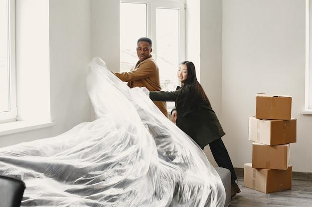 Jonge gelukkige paar in kamer met verhuisdozen in nieuw huis. aziatische en afrikaanse etniciteit.