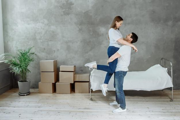 Jonge gelukkige paar man en vrouw in de kamer met verhuisdozen in huis