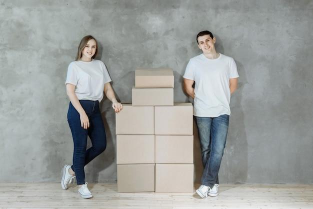 Jonge gelukkige paar man en vrouw staan op de achtergrond van een muur in een nieuw huis onder kartonnen dozen om te verhuizen