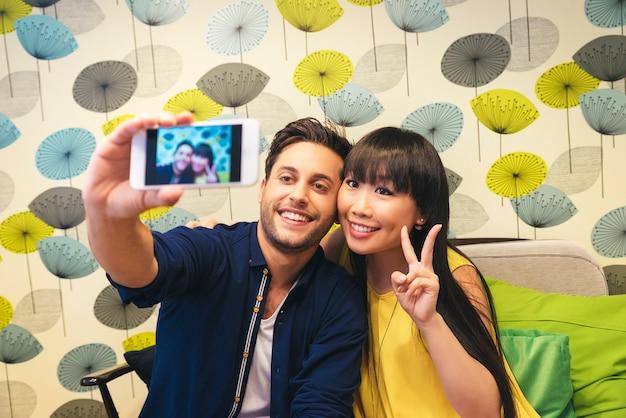 Jonge gelukkige paar met behulp van smartphone in de bar. ze zijn in de coffeeshop
