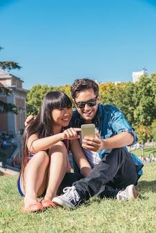 Jonge gelukkige paar met behulp van smartphones zitten in het park