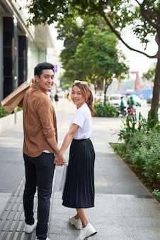 Jonge gelukkige paar met boodschappentassen in de stad.