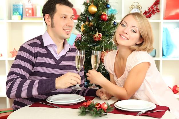 Jonge gelukkige paar met een bril met champagne aan tafel in de buurt van de kerstboom