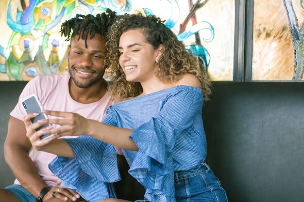 Jonge gelukkige paar nemen een selfie samen met een mobiele telefoon terwijl ze een date hebben.