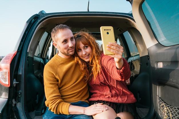Jonge gelukkige paar nemen een selfie zittend in de kofferbak van de auto