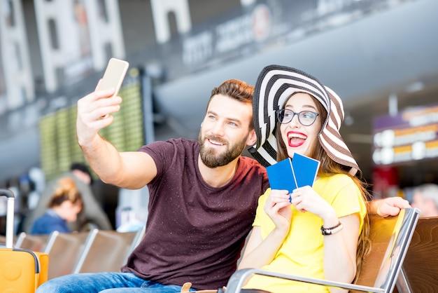 Jonge gelukkige paar selfie foto maken met telefoon in de wachtzaal van de luchthaven tijdens hun zomervakantie