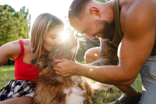 Jonge gelukkige paar spelen met hun hond lachend in park