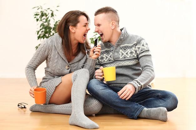 Jonge gelukkige paar thuis lachen