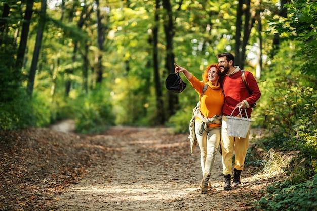 Jonge gelukkige paar verliefd knuffelen en wandelen in de natuur. het paar houdt picknickuitrusting vast.