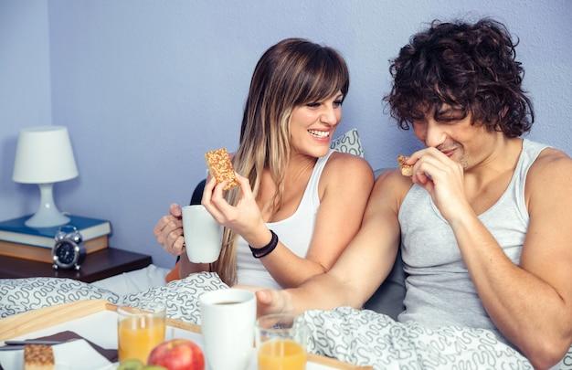 Jonge gelukkige paar verliefd lachen en ontbijten op bed thuis. paar huis levensstijl concept.