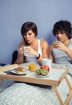 Jonge gelukkige paar verliefd ontbijten op bed geserveerd op een dienblad thuis. paar huis levensstijl concept.