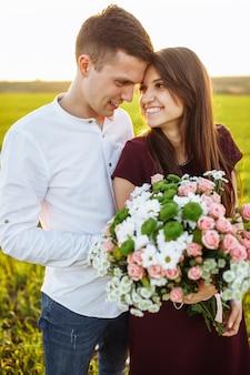 Jonge gelukkige paar verliefd, vrouw met bloemen, gelukkig en geniet van elkaars gezelschap