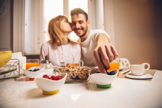 Jonge gelukkige paarzitting door lijst die samen ontbijt hebben bij ochtend. focus op de hand.