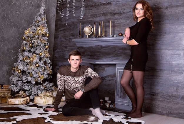 Jonge gelukkige paarzitting voor kerstmisboom