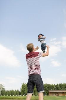 Jonge gelukkige papa zijn zoontje in de lucht overgeven en samen plezier hebben.