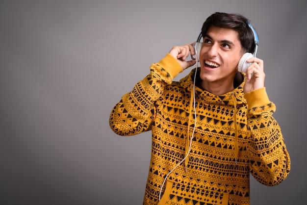 Jonge gelukkige perzische tiener die en muziek met hoofdtelefoons glimlacht luistert