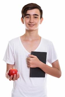 Jonge gelukkige perzische tiener die lacht terwijl hij een rode appel en een notitieboekje vasthoudt