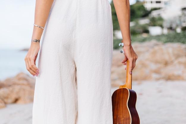 Jonge gelukkige rustige blanke vrouw met ukelele op tropisch rotsachtig strand bij zonsondergang