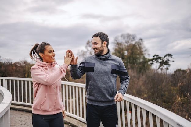 Jonge gelukkige sportieve heteroseksuele vrienden in sportkleding staan op de brug en geven elkaar high five voor prestatie. fitness buitenshuis concept.