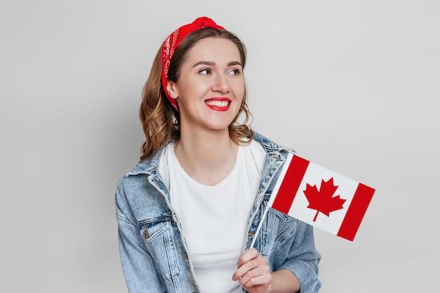 Jonge gelukkige studente die en een kleine vlag van canada glimlacht houdt en weg kijkt geïsoleerd over grijze muur, de dag van canada, vakantie, confederatieverjaardag, exemplaarruimte