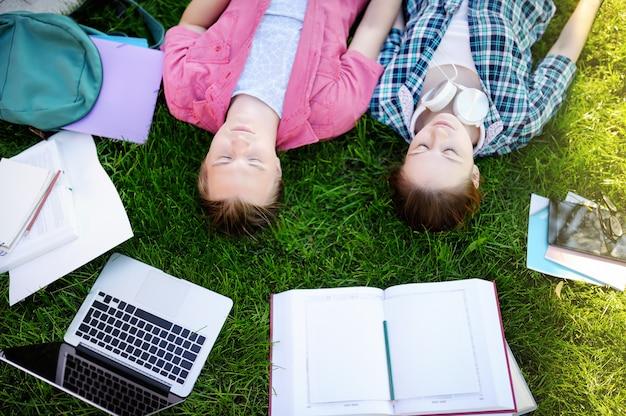 Jonge gelukkige studenten met boeken en notities buitenshuis