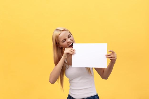 Jonge gelukkige studentenvrouw die lege blocnote toont