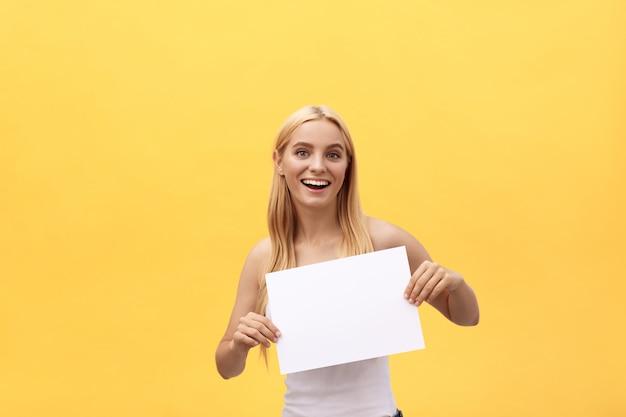 Jonge gelukkige studentenvrouw die lege die blocnote toont, op gele achtergrond wordt geïsoleerd