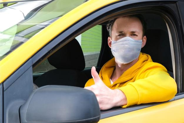 Jonge gelukkige taxichauffeur met beschermend masker zit achter het stuur van een taxi en laat zien zoals