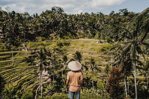 Jonge gelukkige toerist die van het mooie uitzicht op het rijstterras in bali, indonesië geniet. zonnige, ontspannen dag in tegalalang. reisfoto. levensstijl.
