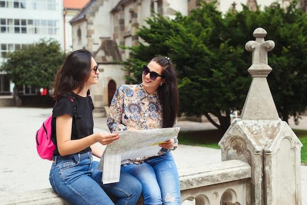 Jonge gelukkige toeristenvrouwen die in stad op vakantie bezienswaardigheden bezoeken