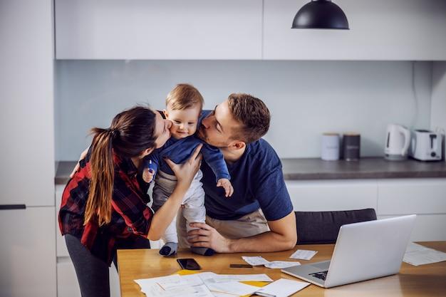 Jonge gelukkige trotse ouders staan in de keuken en kussen hun enige geliefde zoon.
