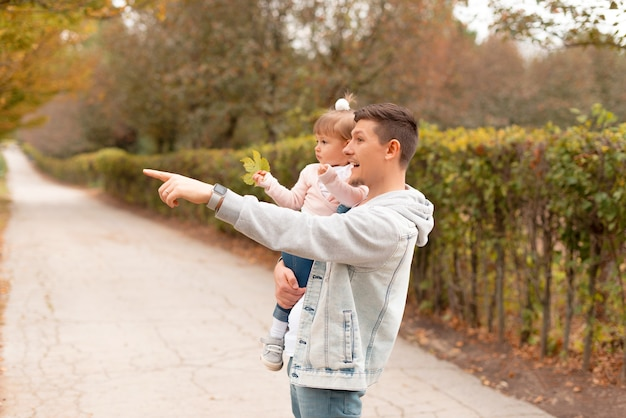 Jonge gelukkige vader die tijd met zijn dochtertje buiten heeft en op iets wijst