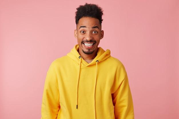 Jonge gelukkige verbaasde afro-amerikaanse man in gele hoodie, hoorde het nieuws dat zijn favoriete band met een concert naar zijn stad komt, breed glimlachend en kijkend.