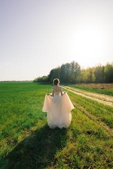 Jonge gelukkige verlaten mooie vrouw in bloeiende tuin. bruid.