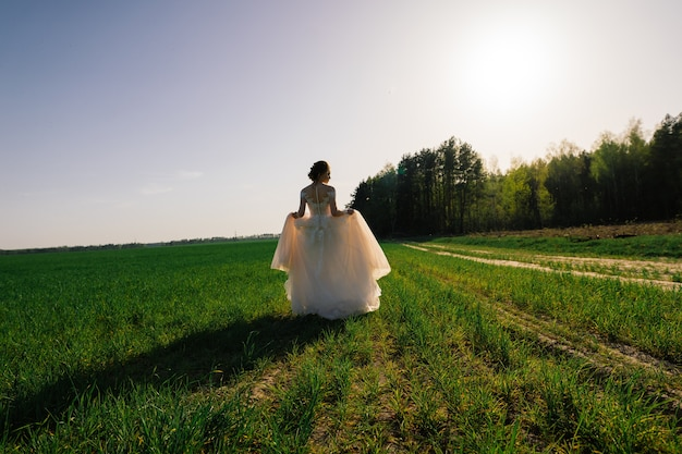 Jonge gelukkige verlaten mooie vrouw in bloeiende tuin.
