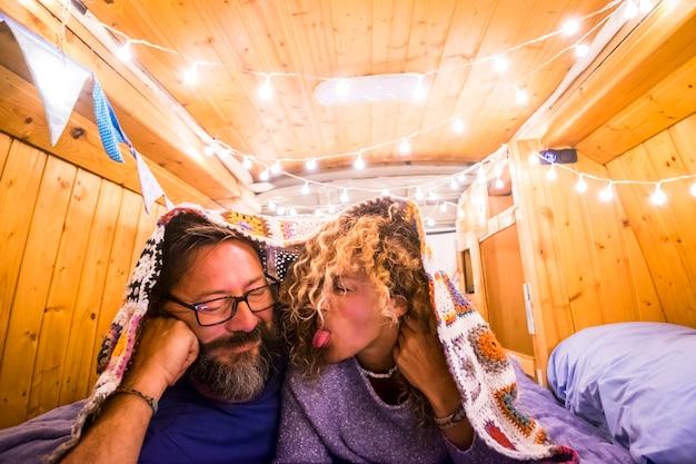 Jonge gelukkige volwassene veel plezier samen liggend op het bed in een klassiek gerestaureerd houten busje dat geniet van een reis-levensstijlvakantie