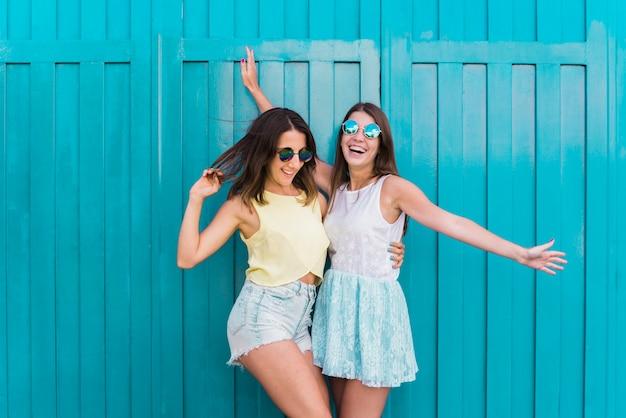 Jonge gelukkige vriendinnen knuffelen en plezier maken