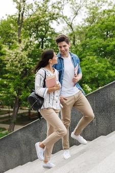 Jonge gelukkige vrolijke geweldige verliefde paar studenten buiten wandelen door stappen met boeken.