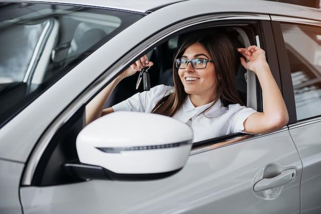 Jonge gelukkige vrouw dichtbij de auto met in hand sleutels