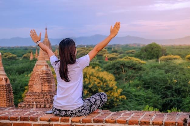 Jonge gelukkige vrouw die, aziatische reiziger op pagode en kijkend reist mooie oude tempels, oriëntatiepunt en populair voor toeristische aantrekkelijkheden in bagan, myanmar. azië reizen concept