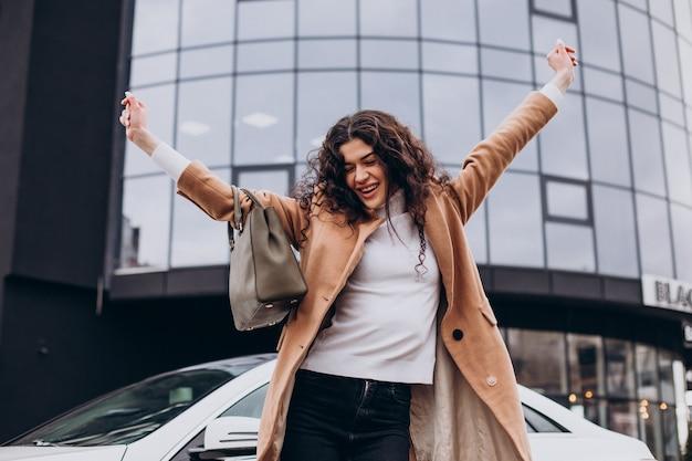 Jonge gelukkige vrouw die bij de auto staat