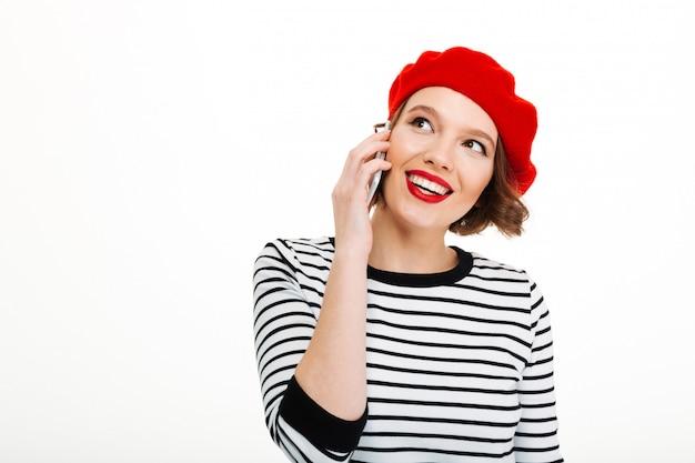 Jonge gelukkige vrouw die door mobiele telefoon spreekt