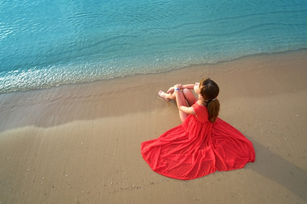 Jonge gelukkige vrouw die een rode jurk draagt die op het zeestrand rust en geniet van een warme zomerochtend.