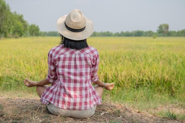 Jonge gelukkige vrouw die geniet van en mediteert met het mooie uitzicht op het rijstterras in azië, thailand. reisfoto. levensstijl. vrouw zit op rijstveld buiten het beoefenen van yoga ontspanning.