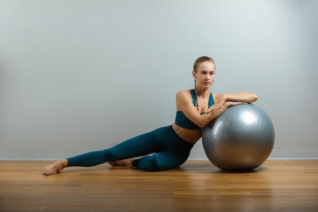 Jonge gelukkige vrouw die geschiktheidsoefeningen met geschikte bal thuis doet